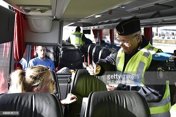 A police officer checks the documents a a passenger inside a bus at Lernacken on the Swedish side of the Oresund strait on November 12 2015 The...