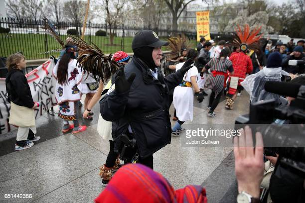 A police officer clears protesters off the sidewalk in front of the White House during a demonstration against the Dakota Access Pipeline on March 10...