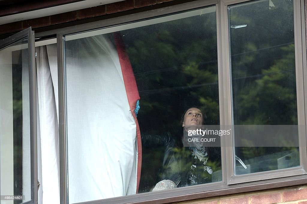 A police officer closes a curtain as she searches the house of Altaf Hussain, the leader of Pakistan's Muttahida Qaumi Movement (MQM) party, in northwest London on June 3, 2014. Hussain has been arrested in London on suspicion of money-laundering, reports said as panic spread through his home city of Karachi and protesters torched vehicles.