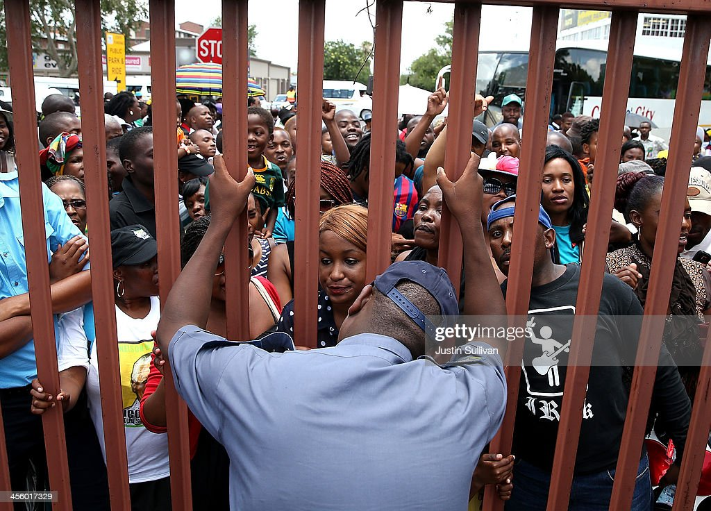 A police officer closes a gate as he cuts off access to buses leaving from the Tshwane Events Centre headed to a line to view the body of former South African president Nelson Mandela as he lies in state at the Union Buildings on December 13, 2013 in Pretoria, South Africa. Nelson Mandela's body will lie in state for three days as part of a week of events commemorating the life of former South African President. Mr Mandela passed away on the evening of December 5, 2013 at his home in Houghton at the age of 95. Mandela became South Africa's first black president in 1994 after spending 27 years in jail for his activism against apartheid in a racially-divided South Africa.