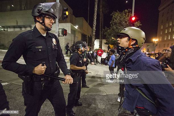 A police officer confronts a demonstrator on November 26 2014 in Los Angeles during demonstrations against a decision by a Ferguson Missouri grand...