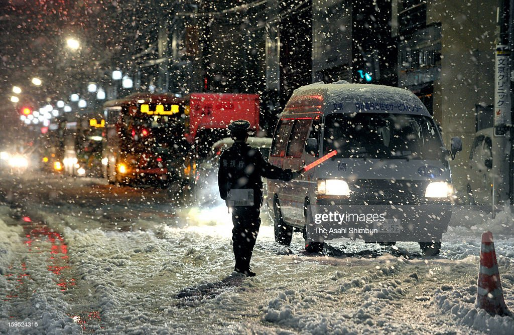 A police officer controls the traffic in the snow on January 14, 2013 in Tokyo, Japan. A strong low pressure system caused heavy snow and strong wind in the coast area including Tokyo, more than 500 injured.
