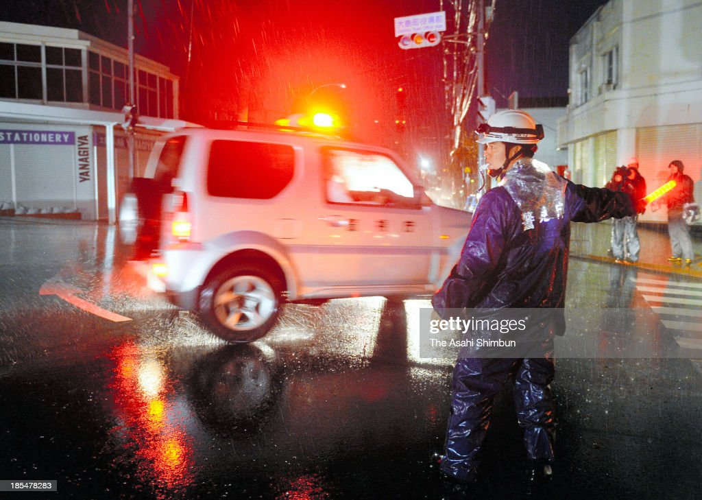 A police officer controls traffic due to power outage near Oshima City Hall on October 20, 2013 in Oshima, Tokyo, Japan. The evacuation advisory was issued October 19 as another heavy rain was expected at a landslide devastated Oshima Island. The early morning downpours from Typhoon Wipha, or No. 26 on October 16 caused landslides that covered 1.14 million square meters and damaged or destroyed 283 homes, according to estimates by Oshima town officials.