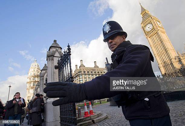 A police officer controls traffic outside the Houses of Parliament in central London on November 25 2015 Britain announced a fresh round of deep cuts...