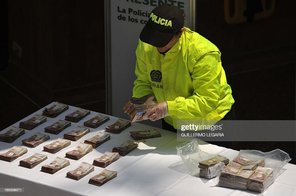 A police officer counts money while a seizure of 102 Kgs of cocaine is presented to the press in the Police heaquarters in Bogota, on April 3, 2013. The drug and 249 Million pesos (US dollars 139 thousand) in cash were seized in a house in the Bogota's neighborhood of Kennedy, and was ready to be marketed in Bogota and also be sent to Eldorado International Airport of Colombian capital, authorities said. AFP PHOTO/Guillermo Legaria