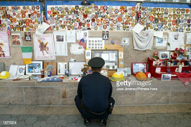 Police officer Daniel Leath from Henderson Nevada visits a memorial wall at Battery Park September 10 2002 in New York City