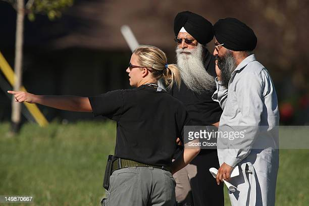 A police officer directs people near the Sikh Temple of Wisconsin where at least one gunman stormed the mass and opened fire August 2012 Oak Creek...