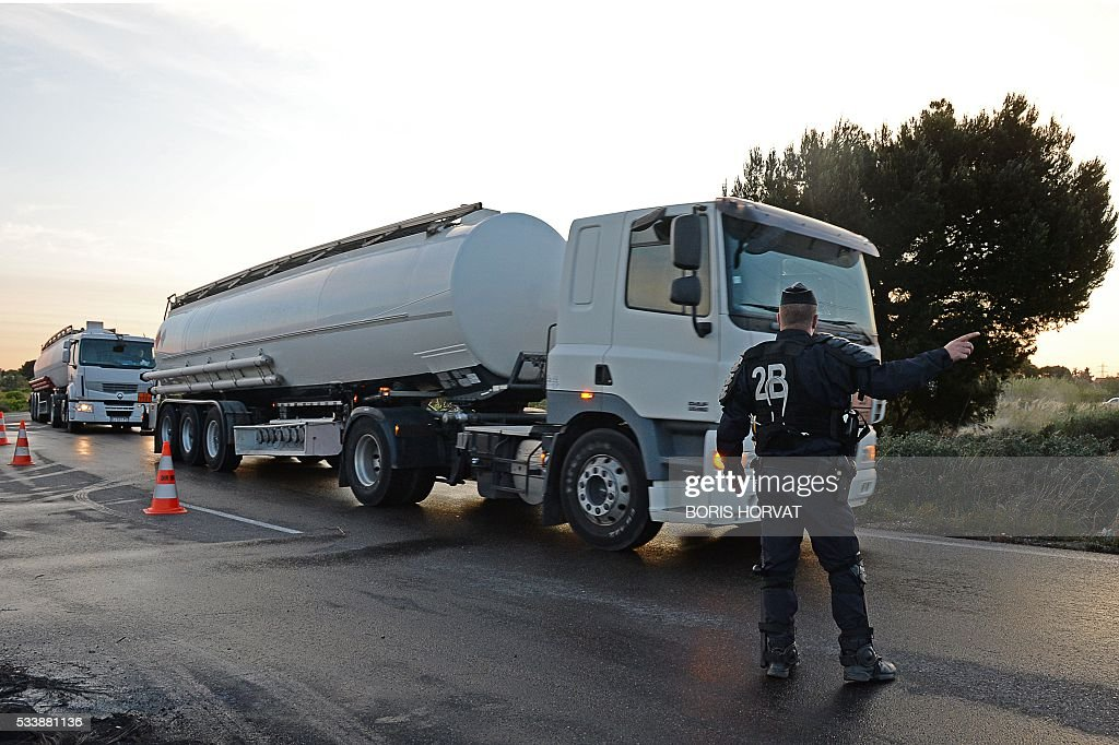 A police officer directs tankers towards the fuel depots in Fos-sur-Mer, southern France, on May 24, 2016, after freeing access to the site which was blocked by workers' union members opposed to government labour reforms. Petrol shortages caused long tailbacks of motorists in parts of France on May 23 as protesters angry over government labour reforms blockaded some of the country's oil refineries and fuel depots. The action was the latest in three months of strikes and protests against the reform, which has set the Socialist government against some of its traditional supporters and sometimes sparked violence. HORVAT