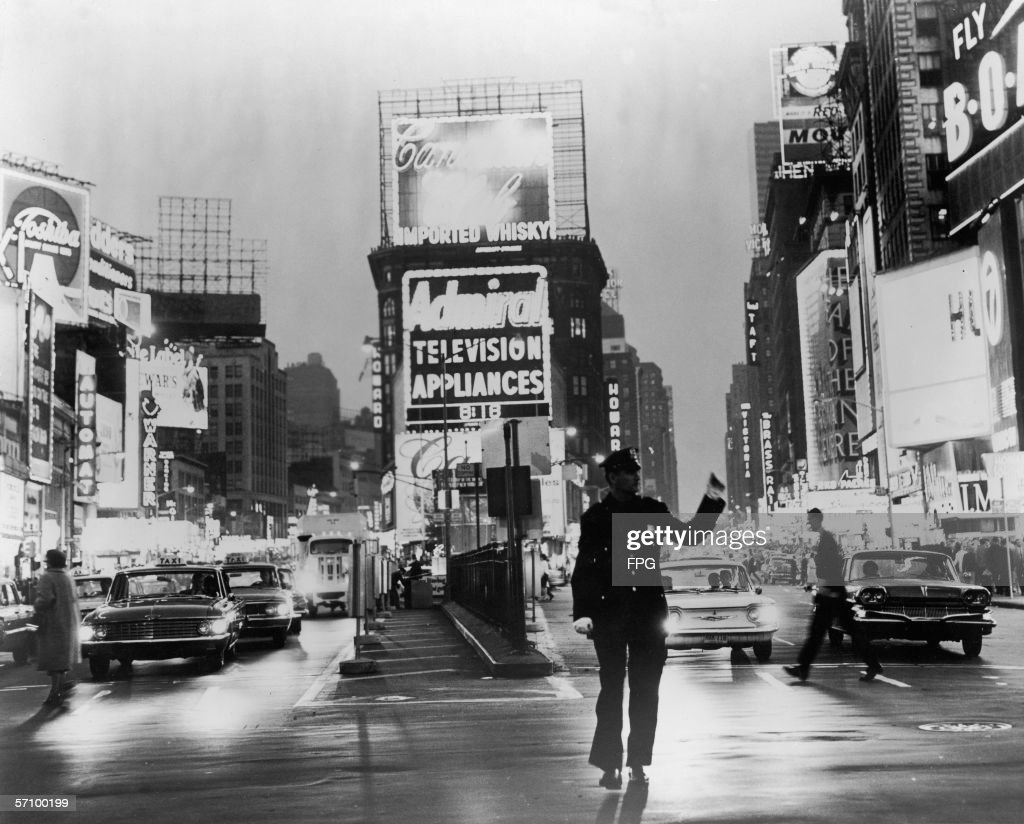 A police officer directs traffic through the neon-lit center of Manhattan's Times Square, New York, New York, early 1964.