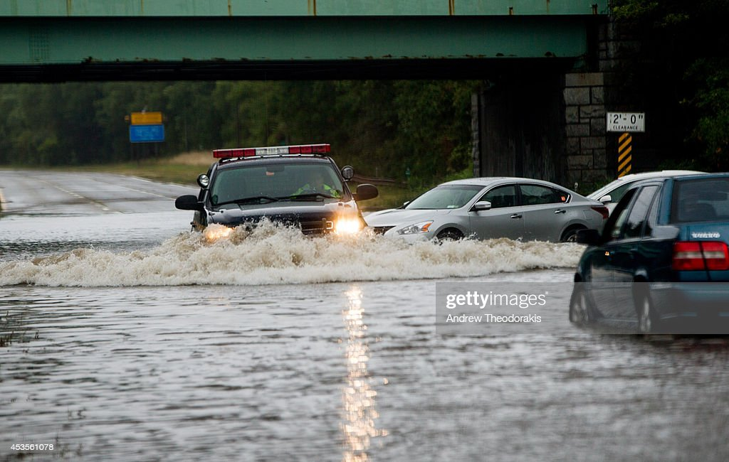 A police officer drives past flooded cars abandoned on the Southern State Parkway following heavy rains and flash flooding August 13, 2014 in Islip, New York. The south shore of Long Island along with the tri-state region saw record setting rain that caused roads to flood entrapping some motorists.