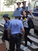 A Police officer escorts a member of female punk band 'Pussy Riot' Nadezhda Tolokonnikova before a court hearing in Moscow on July 23 2012 Three...