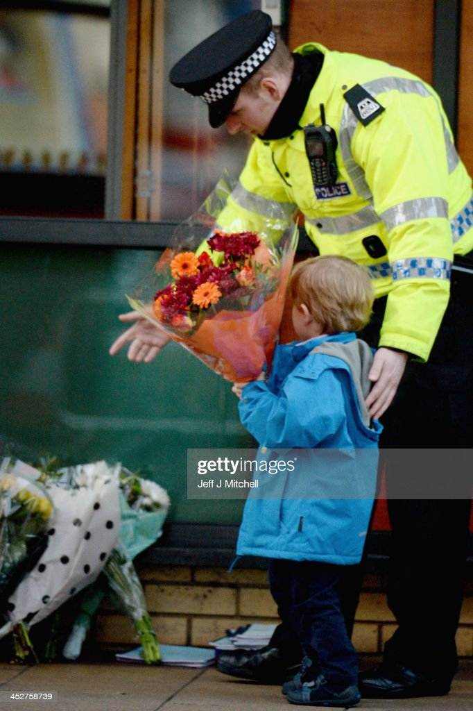 A police officer escorts a young boy as he lays flowers near to The Clutha bar in Stockwell Street where a police helicopter crashed on the banks of the River Clyde, on December 01, 2013 in Glasgow, United Kingdom. The crash which happened at 22:25 on Friday, November 29, has claimed eight lives so far including that of the pilot David Traill, 51, police officer Kirsty Nelis, 36 and Gary Arthur, 48.