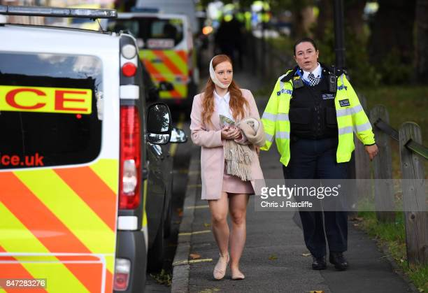 A police officer escorts an injured woman from the scene at Parsons Green Underground Station on September 15 2017 in London England Several people...