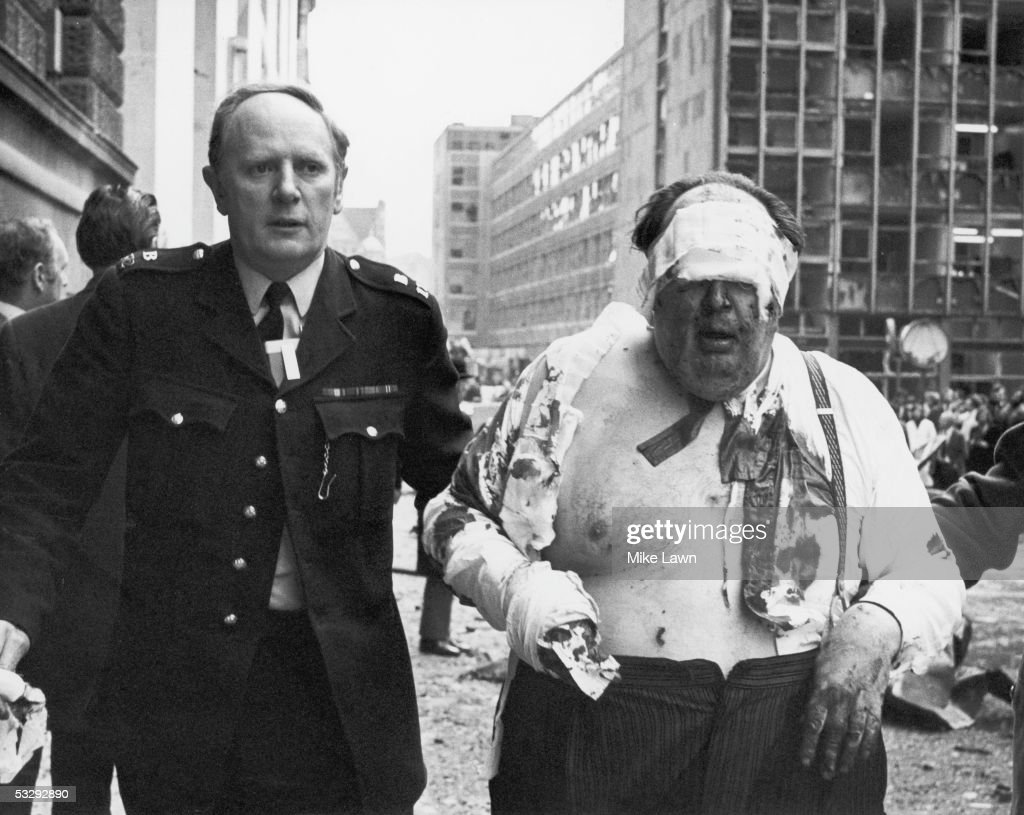 A police officer escorts barrister Caesar James Crespi to safety, after he was injured in an IRA car bomb blast outside the Old Bailey, 8th March 1973.