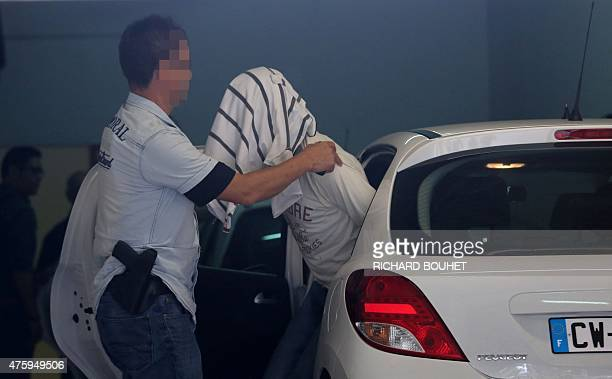 A police officer escorts one of the twin brothers arrested as part of the dismantling of an alleged Jihadist network out of a car at the court of...