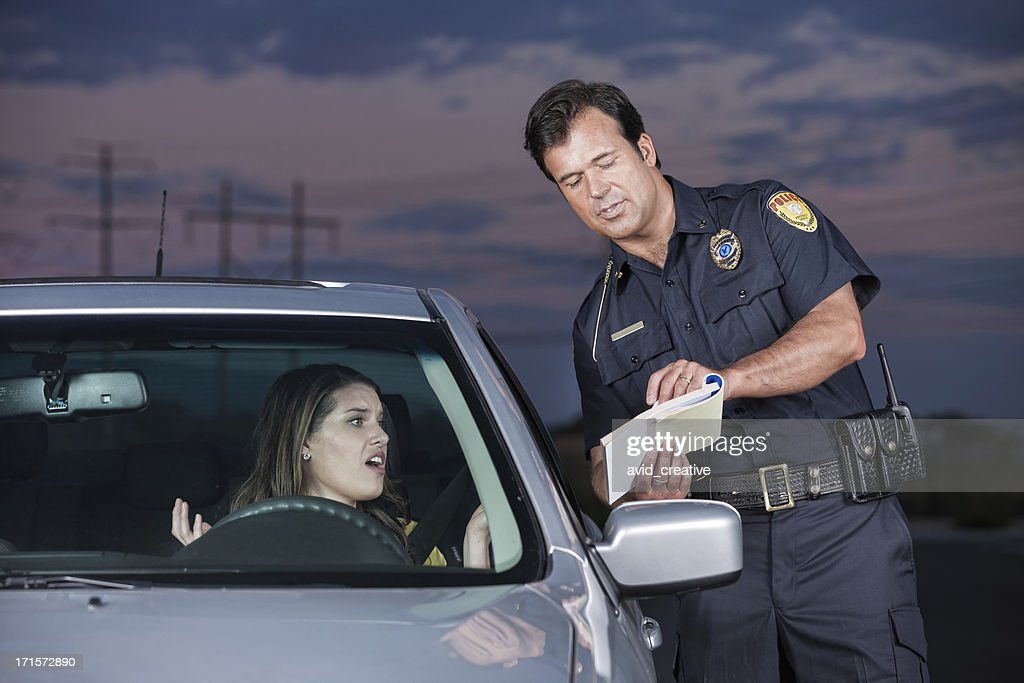 Police Officer Explaining Citation to Woman Driver : Stock Photo