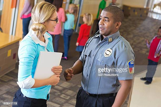 Police officer explaining something to teacher outside her classroom