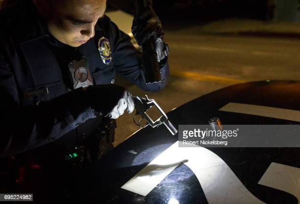 A police officer from the 77th Division gang unit examines a 38 caliber pistol recovered from a roof after it was thrown by a gang member May 21 2017...
