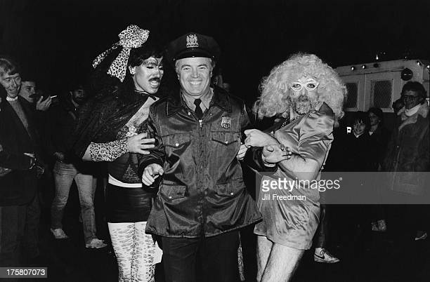 A police officer from the NYPD is accosted by two men in drag on Halloween Sheridan Square Greenwich Village New York City 1983