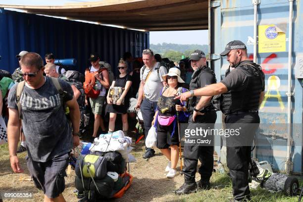 A police officer gestures as festival goers arrive at the Glastonbury Festival amid heightened security at Worthy Farm in Pilton on June 21 2017 near...