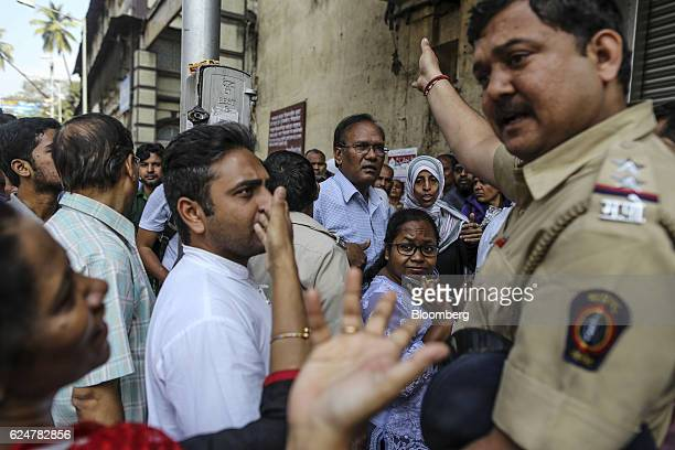 A police officer gestures as he speaks to customers waiting in line to withdraw cash outside a State Bank of India branch in Mumbai India on Saturday...