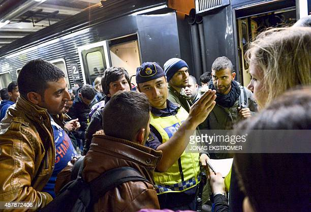 Police officer gestures at the railway station in Stockholm on September 12 after a train with migrants arrived from Malmoe in southern Sweden Many...