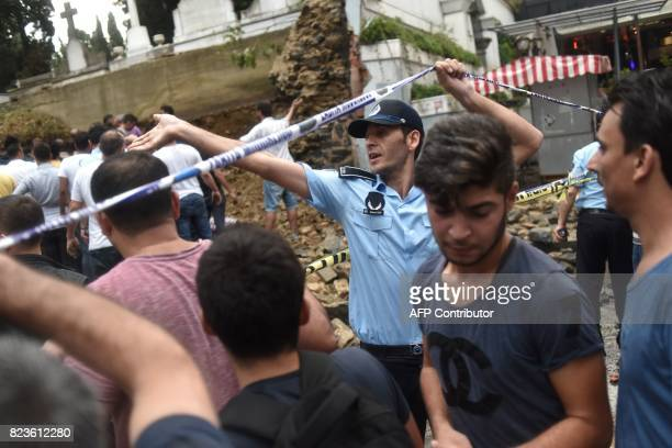 A police officer gestures at the site where a Christian cemetery collapsed in Istanbul on July 27 during a heavy downpour of rain and hail / AFP...
