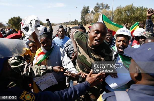 A police officer gestures towards protesters from various Southern African Development Community countries as they demonstrate near the entrance to...