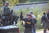 A police officer gets get a break after coming off a search mission as temperatures exceeded 90 degrees during a manhunt for three suspects in the...