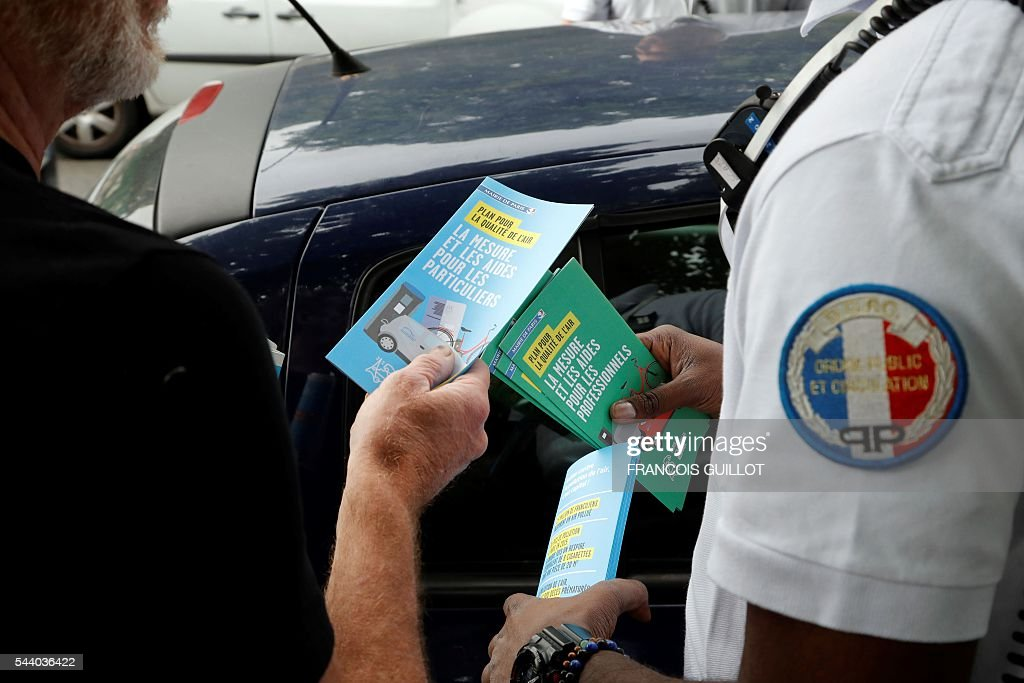 A police officer gives brochures to a motorist after controling his car on July 1, 2016 in Paris as part of the anti-pollution measures aimed at punishing road transports registered before 1997 that are forbidden to be driven during the week. Nearly thirty police officers stood guard on the morning of July 1, in the main squares of Paris to control and raise awareness among the drivers about the new measures concerning road transports adopted by the city and effective from today. Those first controls, mostly to inform and without verbalisation, were organised by the police headquarters and Paris city hall. / AFP / FRANCOIS
