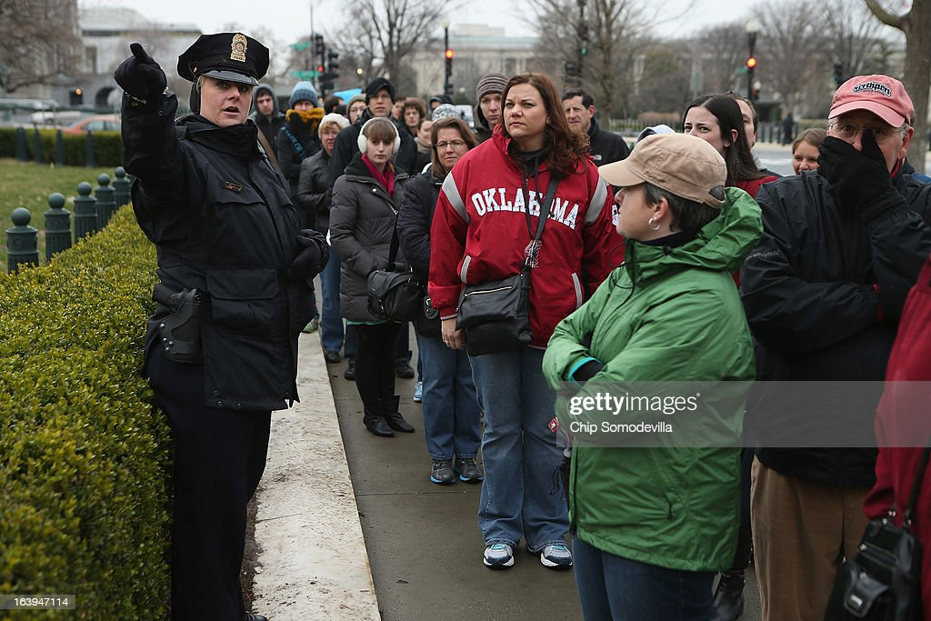 A police officer gives instructions to people standing in line outside U.S. Supreme Court for a chance to hear oral arguements in the case Arizona v. Inter Tribal Council et al. March 18, 2013 in Washington, DC. The court is being asked to deterimine the constitutionality of an Arizona law that requires people to provide documents proving their citizenship before registering to vote under the federal National Voter Registration Act.