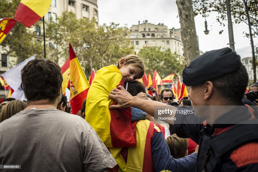 A police officer greets a child wearing a Spanish National flag in support of Spanish unity during a march on Spain's National Day in Barcelona, Spain, on Thursday, Oct. 12, 2017. Prime MinisterMariano Rajoygave his Catalan antagonist Carles Puigdemont five days to clarify whether he has declared independence from Spain or not as the country prepared for its national holiday on Thursday. Photographer: Angel Garcia/Bloomberg via Getty Images