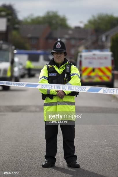 A police officer guards the entrance to a street in the Moss Side area of Manchester on May 28 2017 during an operation A British minister said...