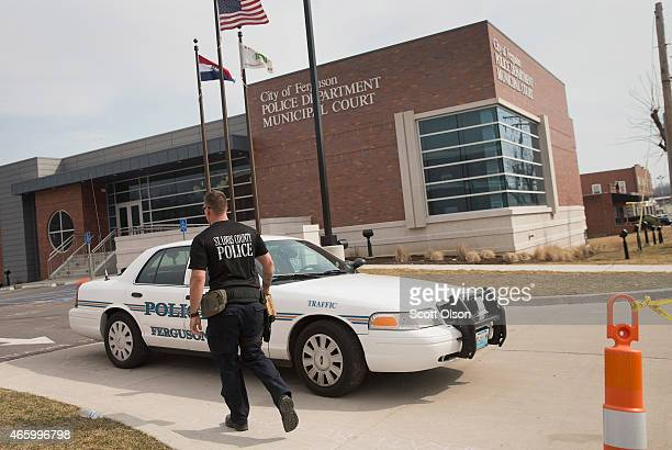 A police officer guards the outside of the police station following an investigation of the area after two officers were shot and wounded during last...