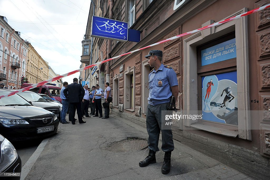 A police officer guards the site of an explosion in the Russian second city of St Petersburg , on July 3, 2013. A package exploded today in a man's hand outside a McDonald's restaurant in St Petersburg, injuring him but causing no other casualties, the RIA Novosti news agency reported.