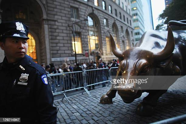 A police officer guards the Wall Street bull as demonstrators associated with the 'Occupy Wall Street' movement face off with police in the streets...