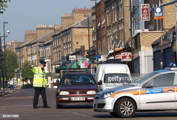 A police officer guides traffic at the scene on Stroud Green Road Finsbury Park north London where two men were injured in a clash between two groups...