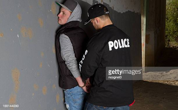 Police officer handcuffing young man against wall