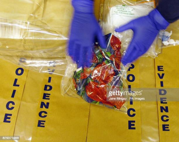 A police officer handles bags containing large amounts of heroin that were seized during a raid late Thursday November 18 at Islington Police Station...