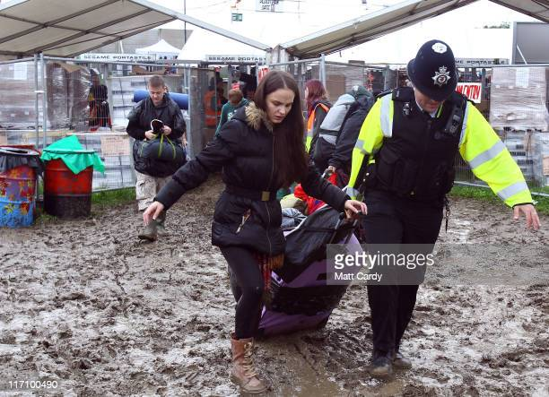 A police officer helps a festival goer with her camping gear as she arrives at the Glastonbury Festival site at Worthy Farm Pilton on June 22 2011 in...