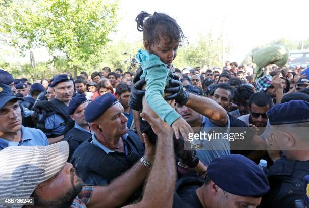 A police officer helps a man with a child as police form a cordon as migrants and refugees board buses at the train station in the city of Tovarnik...