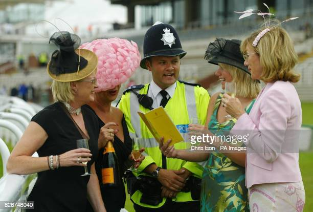 A police officer helps Goodwood members Joyce Wormull Joy Rudge Karen Hill and Pam KempPotter pick their horses on Ladies Day at the racecourse near...