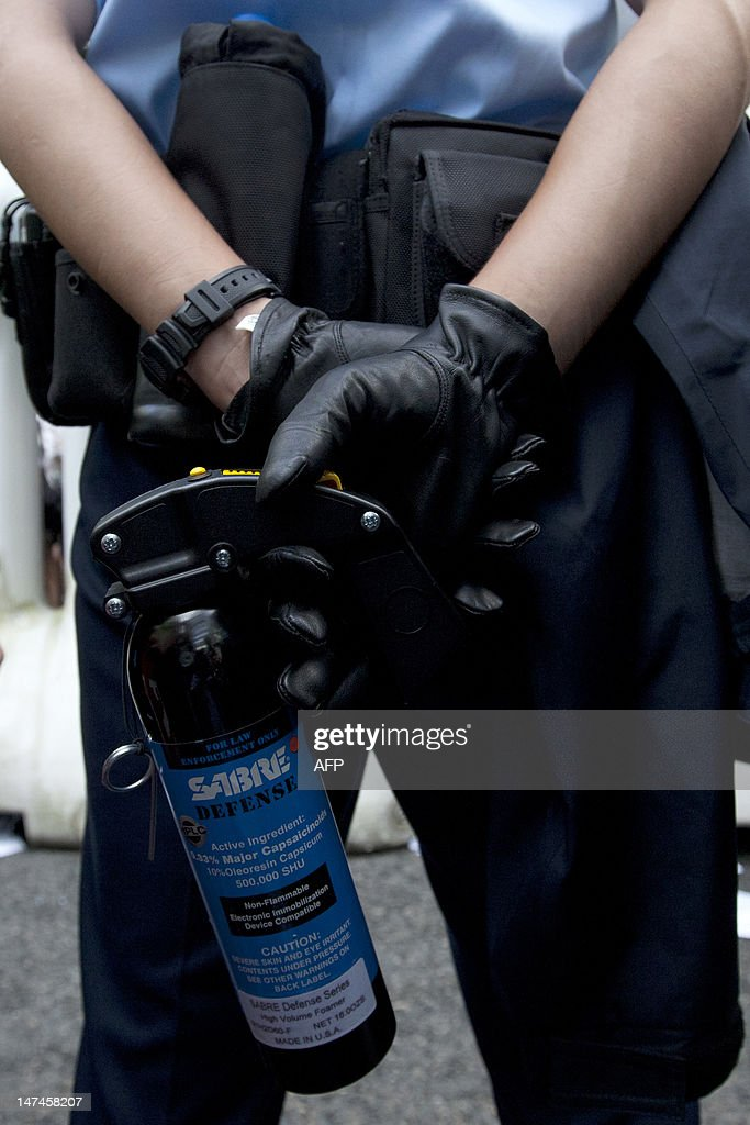 A police officer holds a bottle of pepper spray while standing by at a demonstration on the second day of a visit by Chinese President Hu Jintao on...