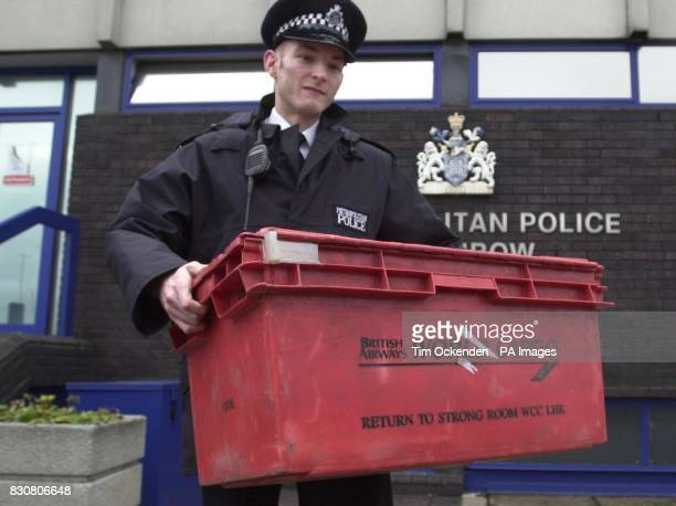 A police officer holds a container similar to the one that contained cash stolen by raiders at London's Heathrow Airport when robbers raided a...