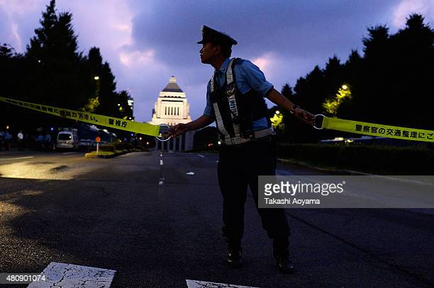 Police Officer holds a police line during a protest outside the National Diet on July 16 2015 in Tokyo Japan The protest is against the security bill...