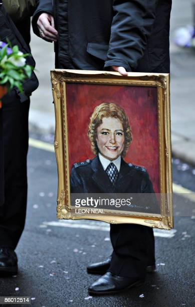 A Police officer holds a portrait of the late PC Yvonne Fletcher before a ceremony to mark the 25th anniversary of her death in St James Square in...