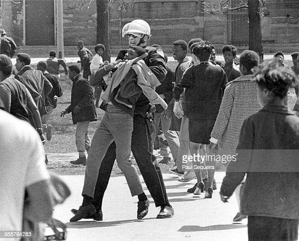 A police officer holds a protestor in a choke hold using his baton near Tilden High School in a south side neighborhood Chicago Illinois 1970s Police...