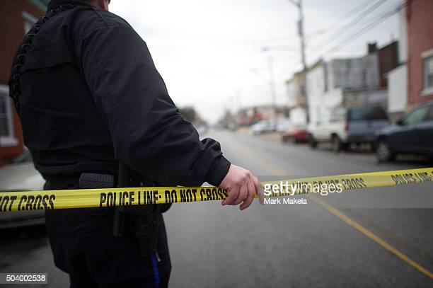 A police officer holds barrier tape several blocks away from the scene of a shooting ambush last night of 33yearold Police Officer Jesse Hartnett who...
