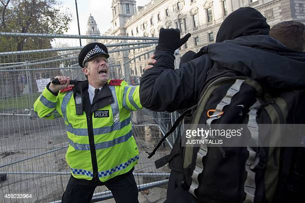 A police officer holds his baton at the ready during a scuffle with a protester during a march against student university fees near the Houses of...