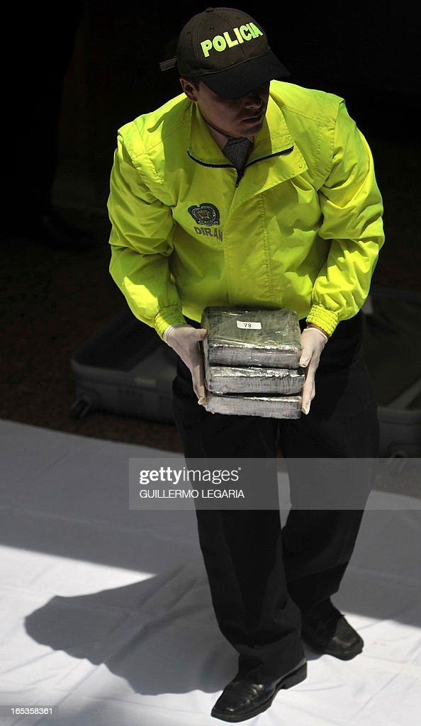 A police officer holds packages containing part of a seizure of 102 Kgs of cocaine, while being presented to the press in the Police heaquarters in Bogota, on April 3, 2013. The drug was seized in a house in the Bogota's neighborhood of Kennedy, and was ready to be marketed in Bogota and also be sent to Eldorado International Airport of Colombian capital, authorities said. AFP PHOTO/Guillermo Legaria